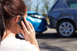 Woman on the phone in front of car accident